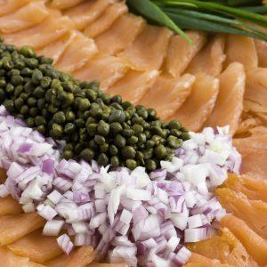 Planche de saumon fumé avec câpres, oignon rouge et fromage à la crème.