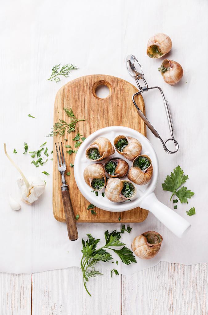 Escargots français mijotés dans du vin blanc, des fines herbes, de l'ail et du beurre. Préparés à la main en France. Un hors-d'œuvre délicieux servi avec du pain frais.