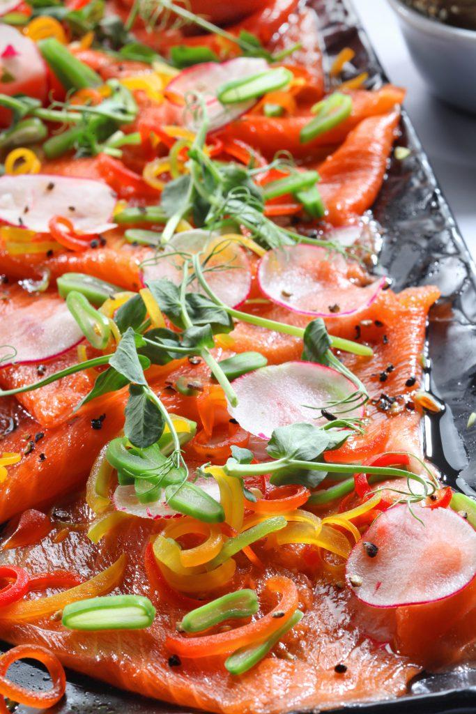 Hors-d'œuvre paléo hors pair, avec saumon fumé, poivron, radis, cresson, graines de sésame, jus de citron et huile d'olive.
