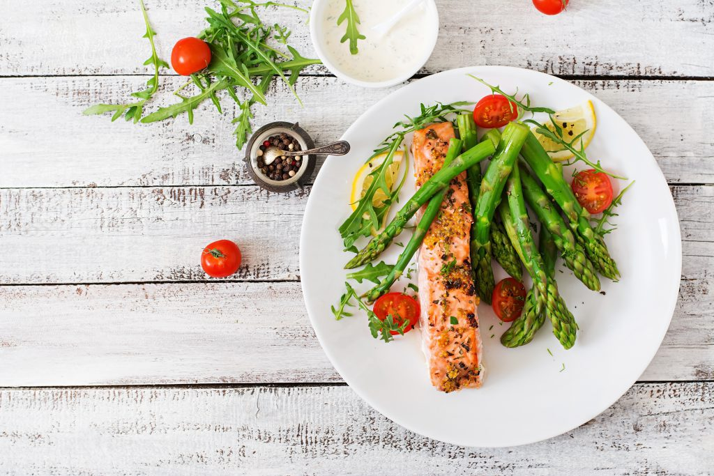 Baked salmon garnished with asparagus, tomatoes, and herbs.