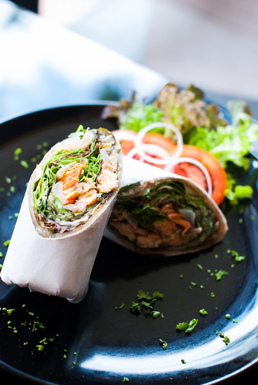 Roasted salmon salad wrap with lemon, capers, mayo, lettuce, tomato, and onion. A great lunch for on-the-go or as a weekday lunch.