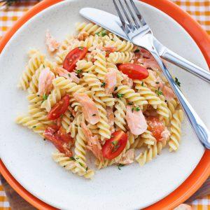 Salade de pâtes avec saumon fumé, aneth, citron, crème sure, légumes au choix comme tomates cerises, pois, poivron et oignon rouge.
