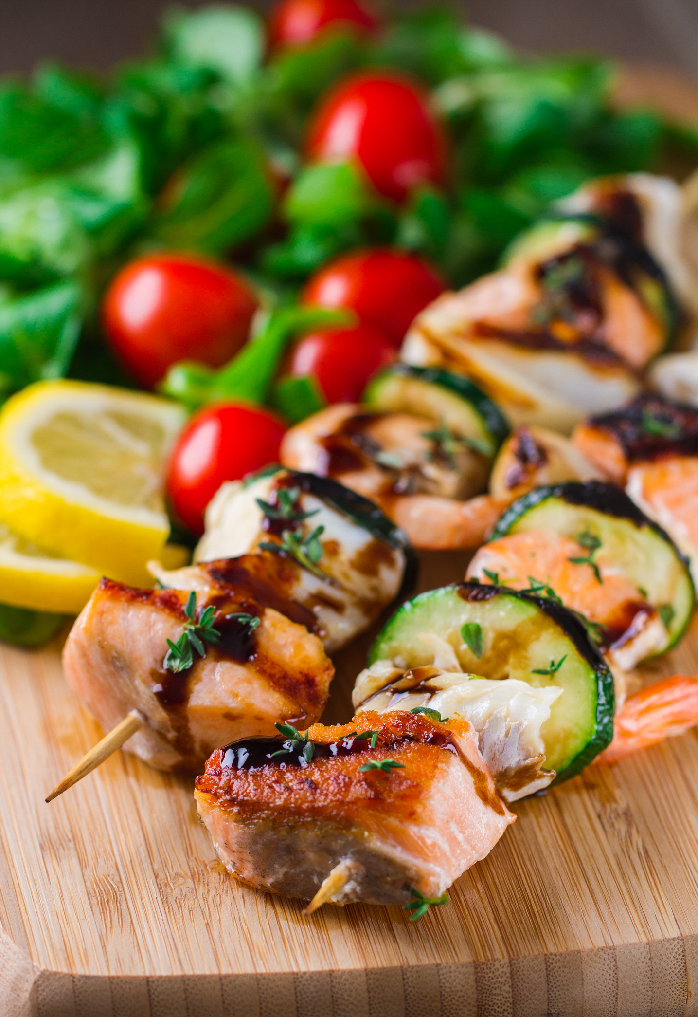 Salmon, shrimp, and veggie skewers on a board