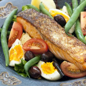 Salad nicoise with salmon, green beans, olives, tomatoes, and hardboiled egg. A delicious and healthy lunch!