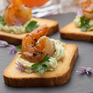 Shrimp and avocado toast with lemon, salt and pepper, and toast.