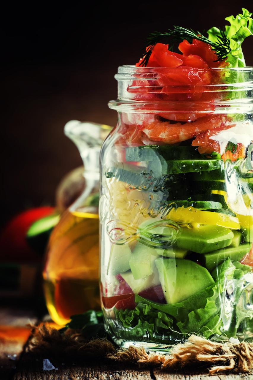 Salade de crevettes citronnées dans un bocal avec crevettes précuites, avocat, huile d'olive, citron, orange, oignon rouge, laitue, concombre et poivron.
