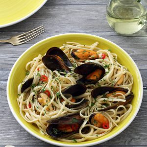 Seafood pasta with mussels, olive oil, garlic, chili flakes, tomatoes, white wine, and parsley. The perfect main for the family or a special evening at home.