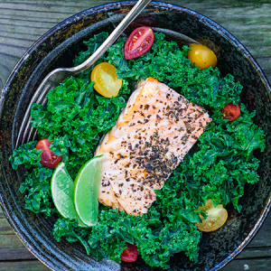 Kale caesar salad with grilled salmon, tomatoes, and lime.