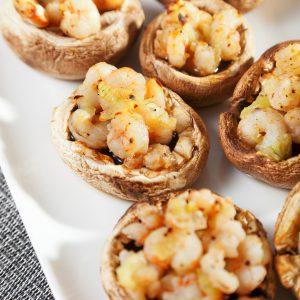 Champignons fourrés aux crevettes arrosés d'un filet de beurre aux herbes et à l'ail.