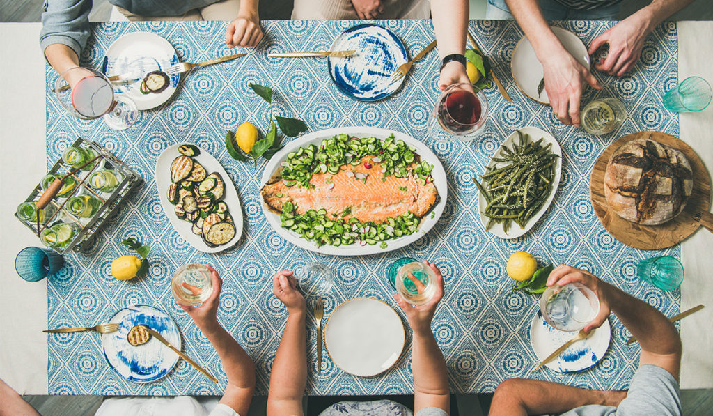 A delicious DOM International salmon dinner with vegetables surrounding.